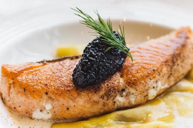 Feche acima do ravioli no molho de creme com cobertura salmon grelhada com caviar.