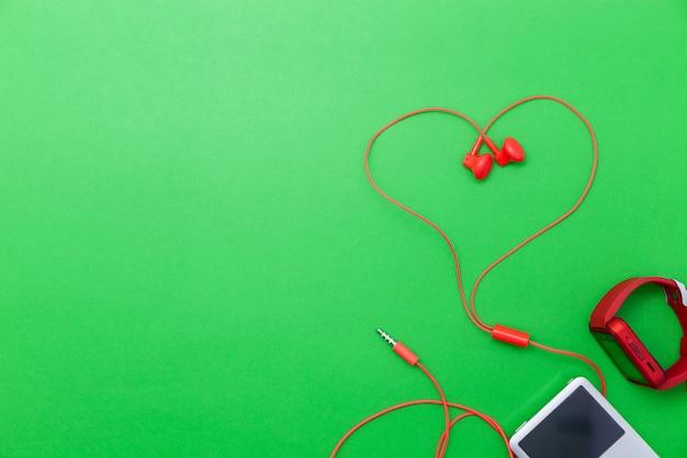 Feche acima do relógio vermelho do esporte e do símbolo vermelho do coração dos fones de ouvido no fundo verde.
