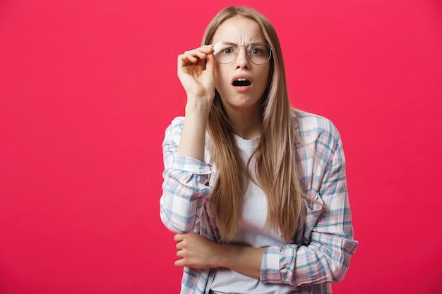 Feche acima do retrato da foto do estúdio da mulher atrativa com a boca aberta que faz a expressão surpreendida louca da emoção fundo cor-de-rosa brilhante isolado