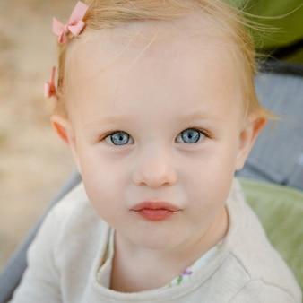 Feche acima do retrato da menina adorável com olhos azuis grandes.