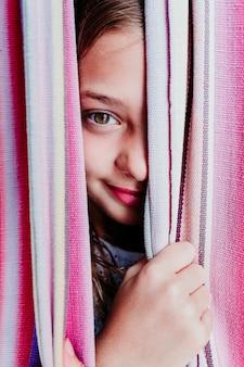 Feche acima do retrato da menina bonita do adolescente que encontra-se na rede colorida no jardim. olhando para a câmera e sorrindo.