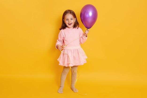 Feche acima do retrato da menina bonito que guarda o balão do puple e os olhares retiraram o levantamento isolado no amarelo, criança fêmea encantador que mantem a boca aberta, tendo a expressão exitedfacial.