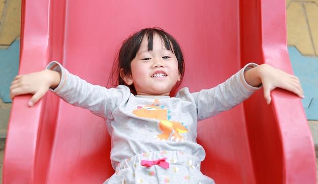 Feche acima do retrato da menina de sorriso feliz da criança que joga o slider no campo de jogos