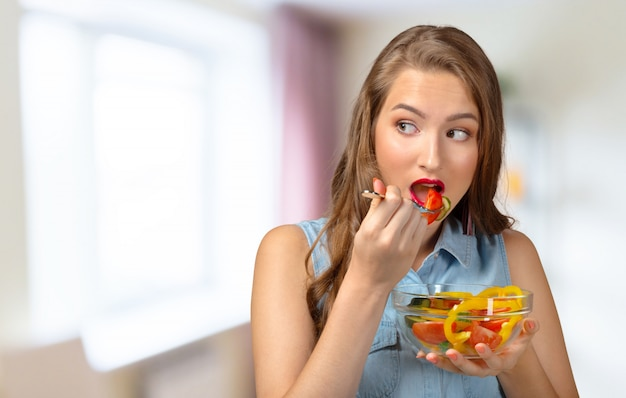 Feche acima do retrato da mulher que come a salada.