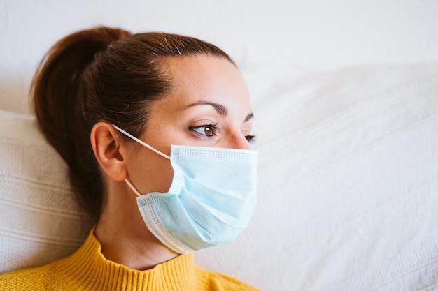 Feche acima do retrato da mulher que desgasta a máscara protetora em casa. conceito de ficar em casa durante o coronavírus covid-2019