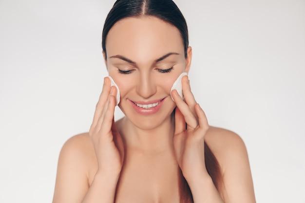 Feche acima do retrato da parede natural semi nua bonita da mulher de beleza pele perfeita pele isolada parede branca. limpeza de tratamento de saúde. conceito de spa de skincare.