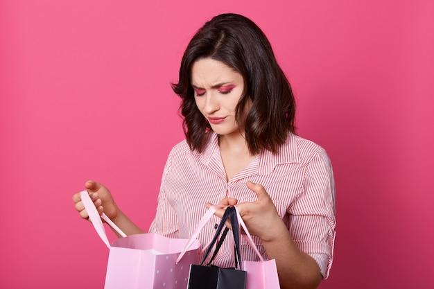 Feche acima do retrato da senhora nova virada que está e que olha no saco de compras aberto em suas mãos com expressão facial triste, estando isolada sobre a parede cor-de-rosa. conceito de compras.