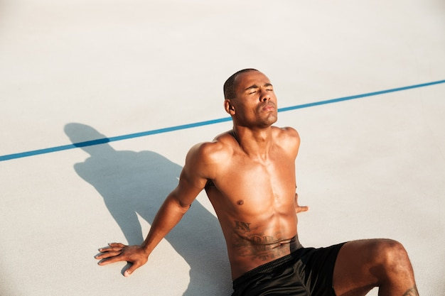 Feche acima do retrato de um desportista afro-americano seminu