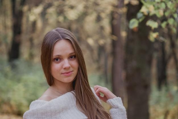 Feche acima do retrato de uma menina bonita na camisola branca perto das folhas de outono coloridas.