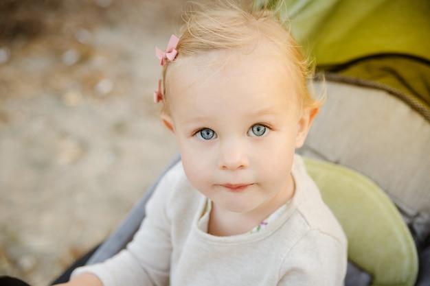Feche acima do retrato de uma menina bonito em um carrinho de criança.