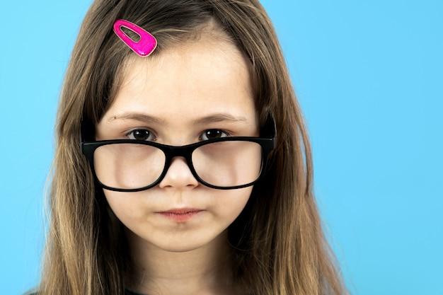 Feche acima do retrato de uma menina da escola infantil que veste os vidros isolados no azul.