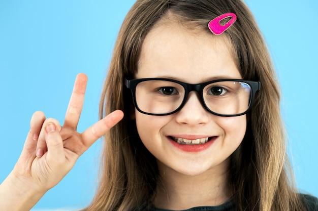 Feche acima do retrato de uma menina da escola infantil que veste os vidros isolados no fundo azul.