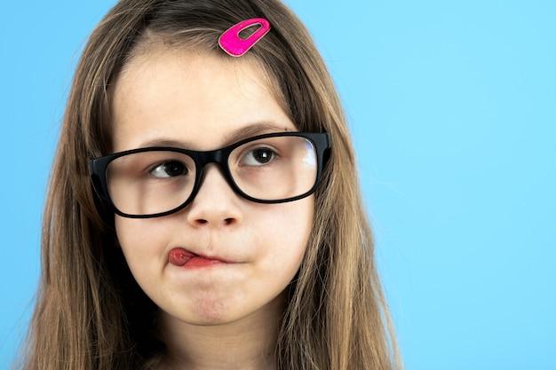 Feche acima do retrato de uma menina engraçada da escola infantil que veste os vidros isolados no fundo azul.