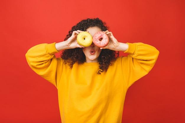 Feche acima do retrato de uma moça bonita satisfeita que come os anéis de espuma isolados sobre o fundo vermelho.
