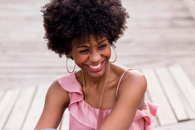 Feche acima do retrato de uma mulher afro-americana bonita nova feliz que senta-se no assoalho de madeira e no sorriso. primavera ou verão. roupa casual