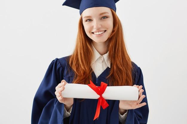 Feche acima do retrato do graduado foxy feliz da mulher no tampão que sorri guardando o diploma. jovem ruiva mulher estudante futuro advogado ou engenheiro.