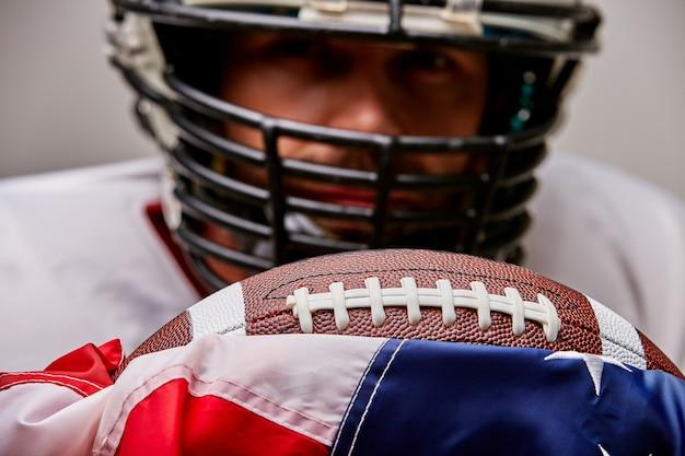 Feche acima do retrato do jogador de futebol americano no capacete com bola e bandeira americana orgulhosa de seu país, em um espaço em branco.