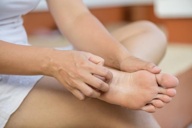Feche acima do risco do pé da mulher o comichão à mão em casa. conceito de saúde e médico.