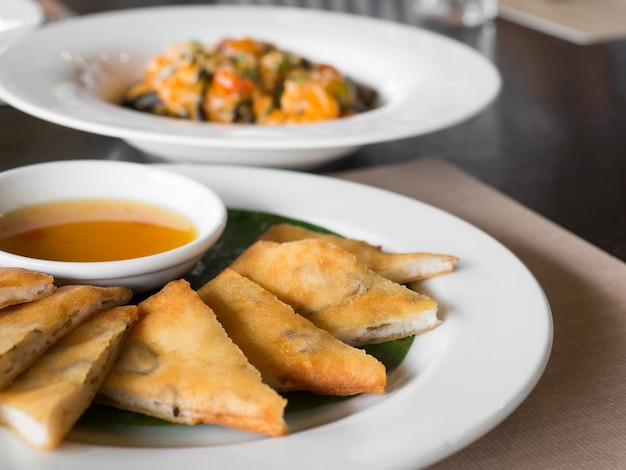 Feche acima do rolo de primavera crocante recheado com camarão e carne de porco em um prato branco em um restaurante