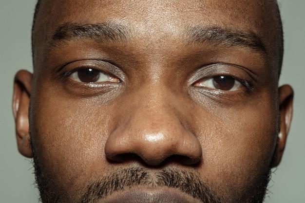Feche acima do rosto do jovem afro-americano bonito, concentre-se nos olhos