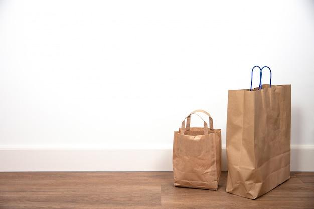 Feche acima do saco de compras marrom contra a parede branca no assoalho de madeira, espaço retro do projeto para o texto