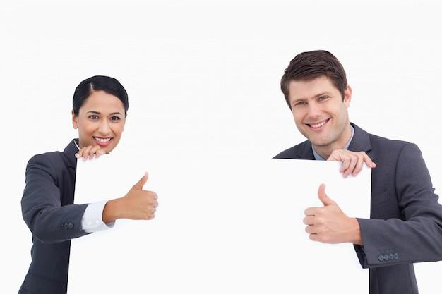 Feche acima do salesteam com sinal em branco dando polegares para cima