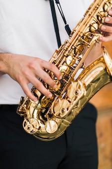 Feche acima do saxofone jogado pelo saxofonista