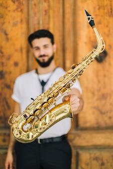 Feche acima do saxofone realizado pelo músico desfocado