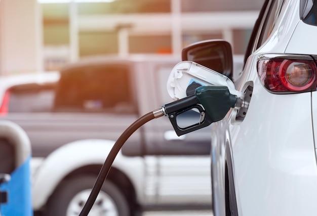 Feche acima do sistema de vigilância do combustível que reabastece um petróleo ao veículo no posto de gasolina.