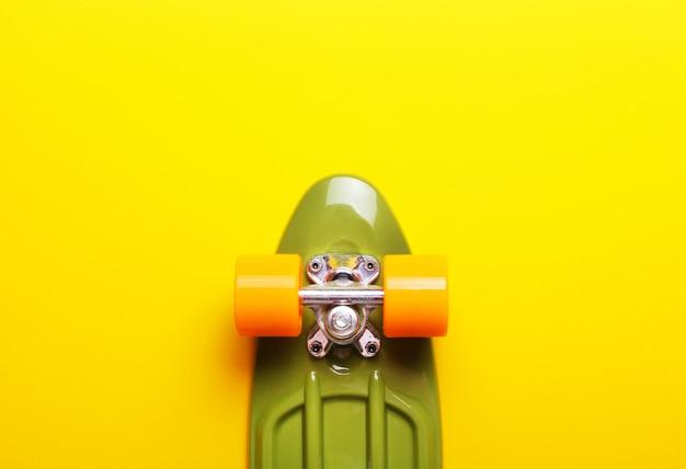 Feche acima do skate verde com as rodas alaranjadas no fundo amarelo.