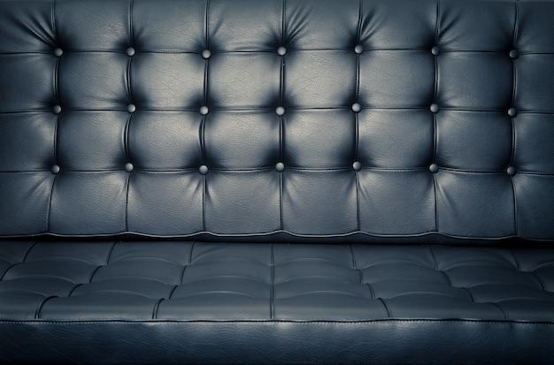 Feche acima do sofá de couro para o fundo