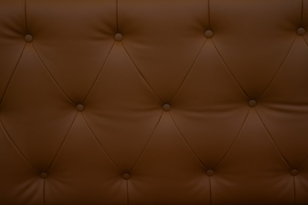 Feche acima do sofá marrom do couro sintético, do fim acima do sofá moderno para o fundo ou da textura.
