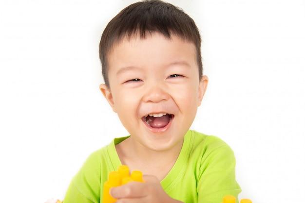 Feche acima do sorriso asiático do menino da criança com cara feliz