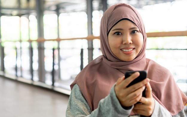 Feche acima do sorriso da mulher muçulmana e mantenha o telefone celular no tempo de relaxamento, conceito dos povos do estilo de vida