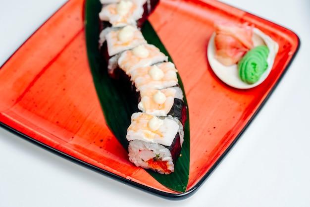 Feche acima do sushi nori coberto com camarão, em fundo branco