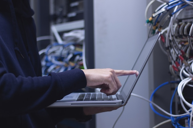 Feche acima do técnico do administrador das mãos que trabalha no portátil no centro de dados.