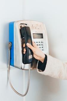 Feche acima do telefone público velho do tubo da boina da mão da fêmea