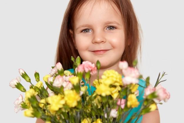 Feche acima do tiro da criança do sexo feminino pequena atraente com aparência agradável
