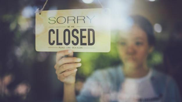 Feche acima do tiro da mão da mulher que gira a placa próxima do sinal na porta de vidro na cafetaria. Foto Premium