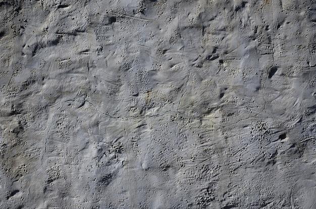 Feche acima do tiro da parede da argila do marrom do grunge em uma casa velha. a mistura de algum outro objeto, como madeira e pedra