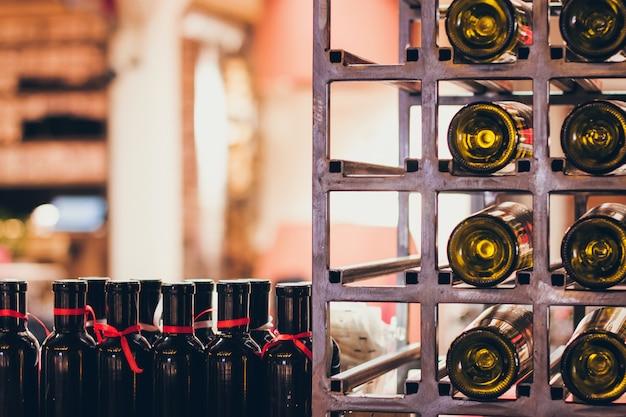 Feche acima do tiro da prateleira de vinho com muitas garrafas