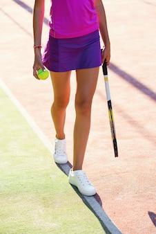 Feche acima do tiro da tenista atraente de uniforme com raquete e bola andando na quadra de tênis ao ar livre no fundo por do sol.