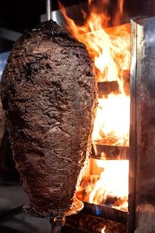 Feche acima do tiro da torrefação de carne empilhada para ser usado na preparação dos giroscópios gregos tradicionais do prato ou doador turco do durum. shawarma