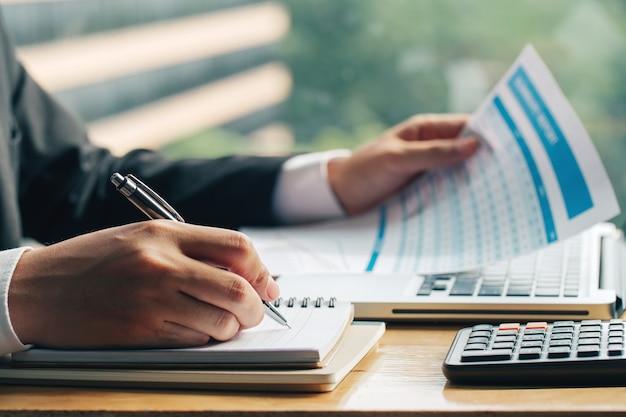 Feche acima do tiro das mãos do homem de negócios com caneta escrevendo notas em um papel e por outro lado, segurando o gráfico de marketing.
