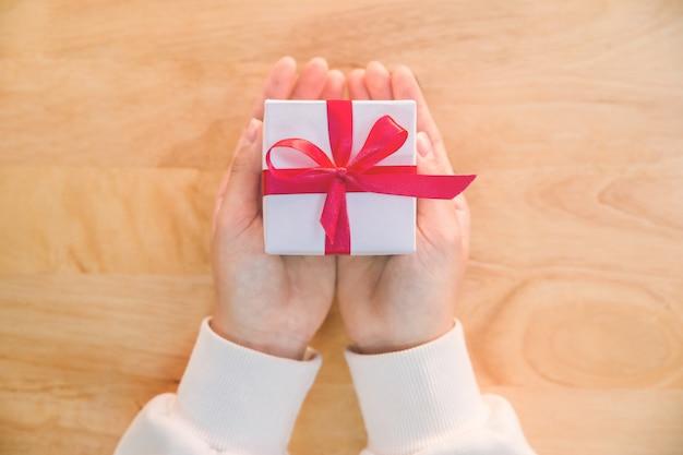 Feche acima do tiro das mãos fêmeas que mantêm um presente pequeno envolvido com fita vermelha.