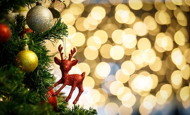 Feche acima do tiro de itens de decoração de véspera de natal brilhante vermelho pendurado decoração no galho de árvore de pinho de natal verde com bolas de esfera e outras coisas ornamentais na frente turva fundo de bokeh luz.