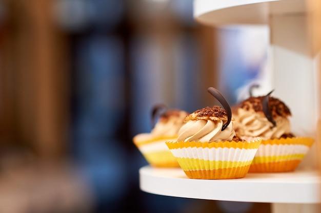 Feche acima do tiro de queques da baunilha do caramelo com alimento do copyspace da decoração do creme e do chocolate que come o conceito do doce do açúcar.