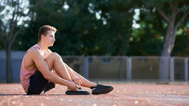 Feche acima do tiro do atleta jovem macho esticando a perna na pista de corrida no estádio, preparando-se para malhar. homem caucasiano, exercitando-se ao ar livre, vestindo roupas esportivas azuis. esporte, pessoas, estilo de vida