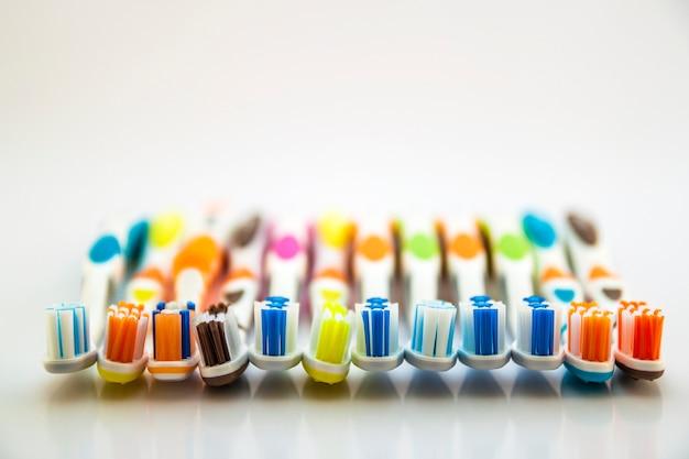 Feche acima do tiro do grupo de escovas de dentes coloridos no toalete limpo no branco, conceito dental.