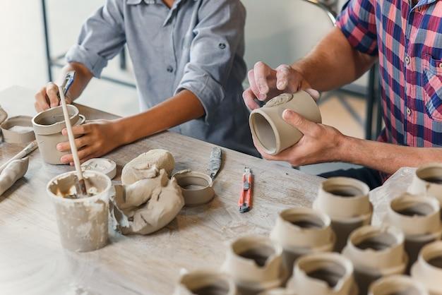 Feche acima do tiro do homem caucasiano envelhecido médio e o rapaz pequeno trabalha junto com os copos de barro na oficina de cerâmica.